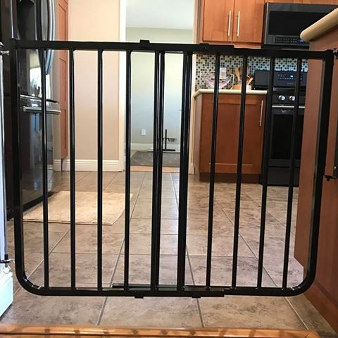 Black child safety gate installed at entrance of kitchen.