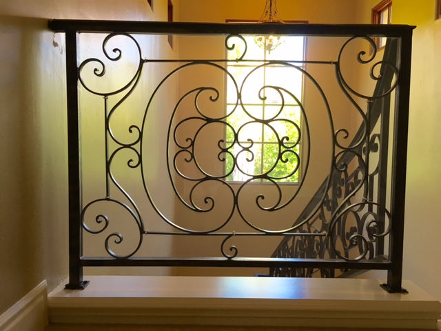 Decorative iron stair banister that has been babyproofed